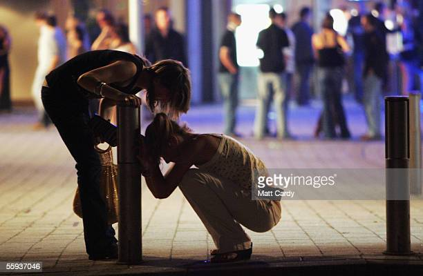 A reveler stops to help her friend after leaving a bar in Bristol City Centre on October 15 2005 in Bristol England Pubs and clubs prepare for the...