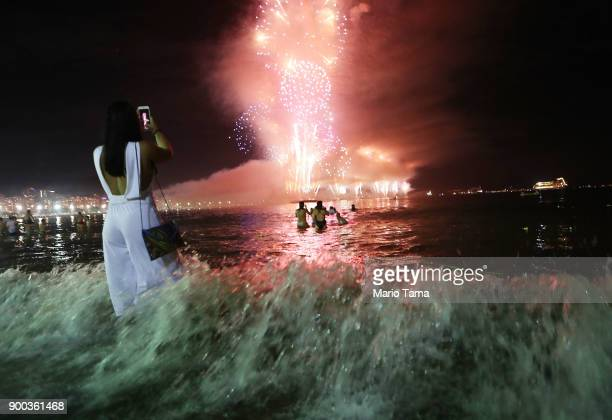 A reveler takes photos as fireworks launched from barges explode over Copacabana beach on January 1 2018 in Rio de Janeiro Brazil Fireworks were...
