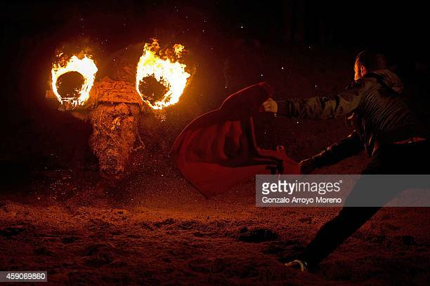 A reveler uses a jersey as a cape ahead of a bull with flammable balls attached to it's horns during the 'Toro de Jubilo' fire bull festival on...