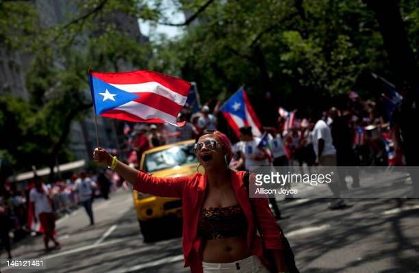 A reveler walks down Fifth Avenue during the Puerto Rican Day Parade on June 10 2012 in New York City The Puerto Rican Day Parade draws hundreds of...