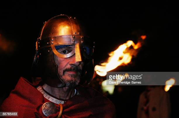 A reveler walks with a torch during the first of the Bonfire Night celebrations on September 24 2005 in Burgess Hill England Bonfire Night is related...