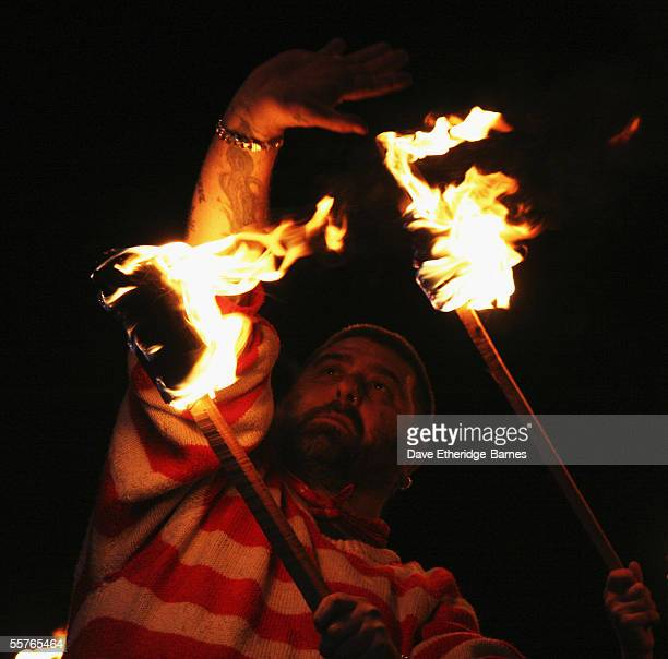 A reveler walks with torches during the first of the Bonfire Night celebrations on September 24 2005 in Burgess Hill England Bonfire Night is related...