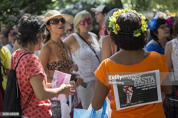 Reveler wears a sign protesting against a local politician during the Bloco das Mulheres Rodadas Carnival parade in Rio de Janeiro, Brazil, on...
