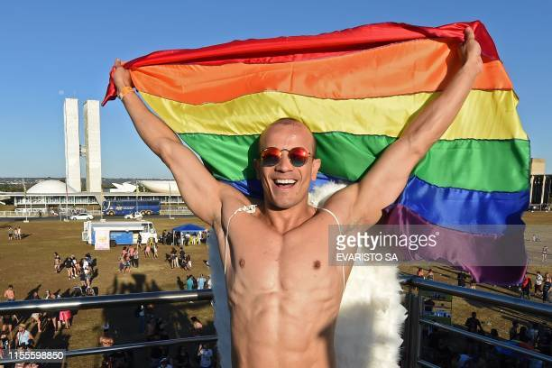"""Reveler with a rainbow flag takes part in the 22nd LGBT Pride Parade, which theme is """"50 years of Stonewall"""", in Brasilia, on July 14, 2019."""