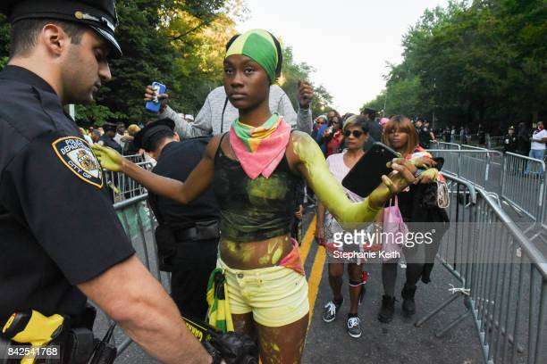 Revelers are searched by police officers during a Caribbean street carnival called J'ouvert on September 4 2017 in the Brooklyn borough of New York...