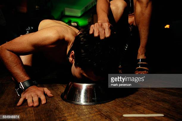 Revelers at La Nouvelle Justine a French bistro with a sadomasochistic theme A dominatrix forces a submissive man to eat from a dog food dish on the...