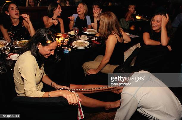 Revelers at La Nouvelle Justine a French bistro with a sadomasochistic theme A submissive African American man licks a young woman's foot as her...