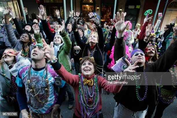 Revelers beg for beads to be tossed from a balcony in the French Quarter during Mardi Gras day on February 16 2010 in New Orleans Louisiana The...