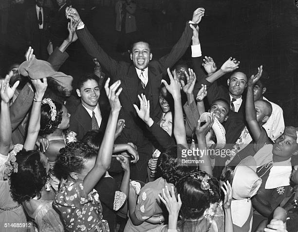 Revelers carry Ossie Moss a bellhop elected king of the Negro Cotton Carnival along famous Beale Street in Memphis Tennessee