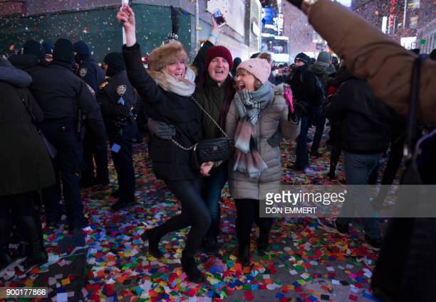 Revelers celebrate as the ball drops to welcome in the new year during New Year's Eve celebrations in Times Square on January 1 2018 in New York /...