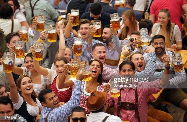 Revelers cheer with 1-liter-mugs of beer during the opening weekend of the 2019 Oktoberfest on September 21, 2019 in Munich, Germany. This year's...