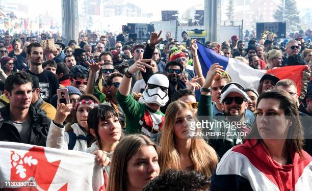 Revelers dance as a DJ perfors during the first winter edition of the Tomorrowland electronic music festival in l'Alpe d'Huez eastern France on March...