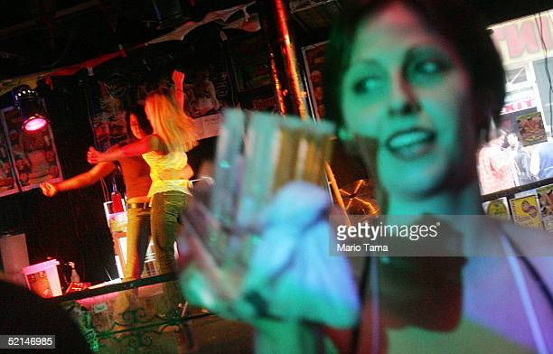Revelers dance in a bar as a waitress carries shots of alcohol during Mardi Gras festivites February 6 2005 in New Orleans Louisiana Festivities will...