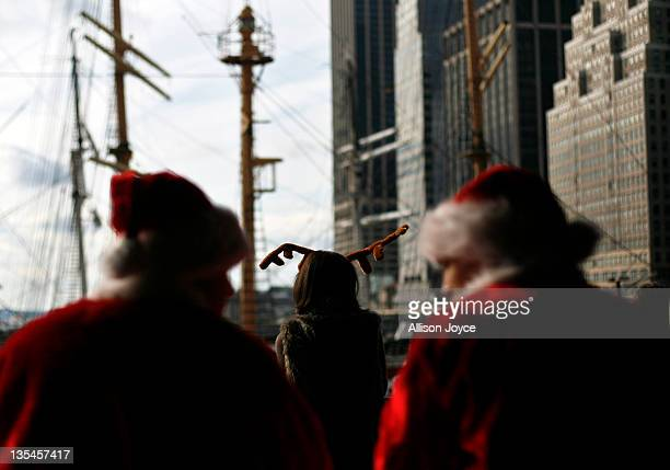 Revelers dressed as Santa Claus and Rudolph the Reindeer gather at the South Street Seaport during the annual SantaCon event December 10 2011 in New...