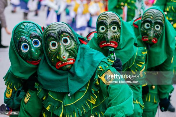 Revelers dressed in traditional colorful costumes and painted wooden masks take part in the annual Fasnet carnival parade on February 4 2018 in...