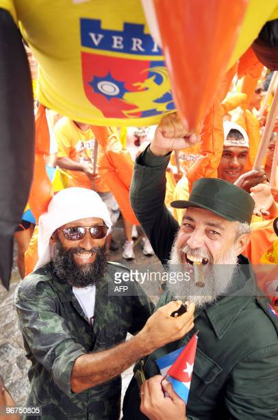 Revelers dressed up as Al Qaeda leader Osama Bin Laden and former Cuban President Fidel Castro dance among the traditional giant dolls along the...