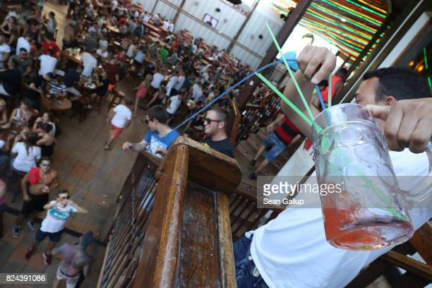 Revelers feed a cocktail through connected straws down to a friend while partying at the Bierkoenig beer hall near the Ballermann stretch on July 27...