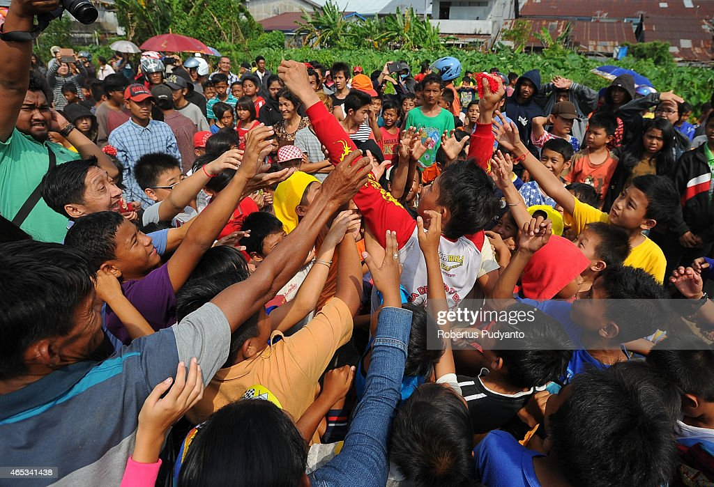 PONTIANAK, KALIMANTAN, INDONESIA - MARCH 06: Revelers fight over for the red thread from a Chinese Dragon during Cap Go Meh celebrations on March 6, 2015 in Pontianak, Kalimantan, Indonesia. The Chinese Dragon dance is often performed during Chinese New Year celebration, as it is believed to bring good improvements in health, prosperity, and fortune. Cap Go Meh Festival also know as the Lantern Festival is celebrated on the 15th day of the Chinese Lunar Year and the Dragons are burnt to mark the end of Chinese New Year celebration.
