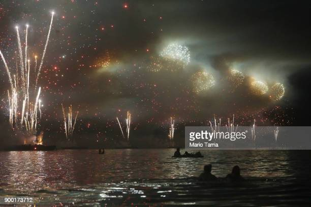 Revelers float on the water while watching fireworks launched from barges explode over Copacabana beach on January 1 2018 in Rio de Janeiro Brazil...