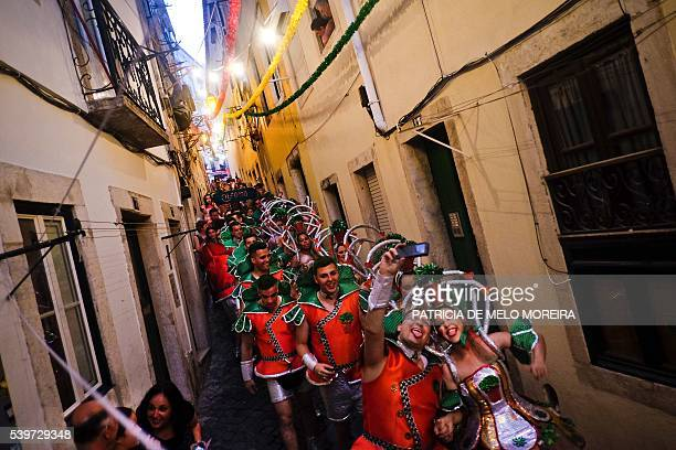 Revelers from a typical Lisbon neighborhood Alfama walk through the neighborhood streets on their way to the Saint Anthony's Parade on Avenida da...