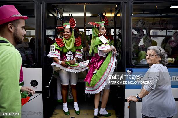 Revelers from one of Lisbon's neighborhoods Alfama stand inside a bus on their way to the Saint Anthony's Parade on Avenida da Liberdade in Lisbon on...