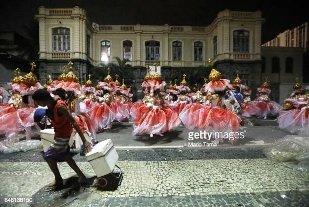 Revelers from the Portela samba school wait to perform as a street vendor walks past outside the Sambodrome in the early morning hours during...