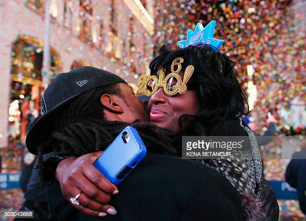 TOPSHOT Revelers hug after the ball drop during New Year's Eve celebrations in Times Square on January 1 2016 in New York AFP PHOTO/ KENA BETANCUR /...