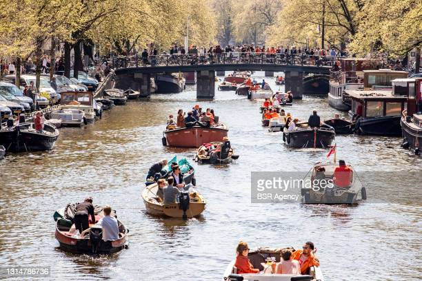 Revelers in boats are seen on the canals during King's Day 2021 on April 27, 2021 in Amsterdam, Netherlands. Due to the coronavirus pandemic, this...