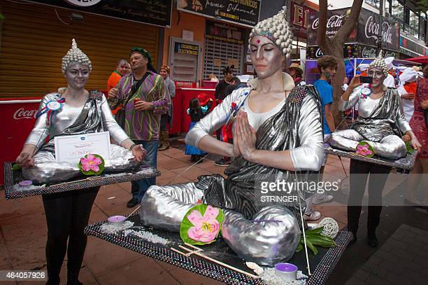 Revelers in budha style fancy dress pose during the last daytime event of the Santa Cruz de Tenerife carnival themed this year on the future in Santa...