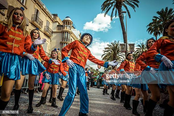 Revelers in their colorful costumes dance in the street during the children carnival parade in Sitges