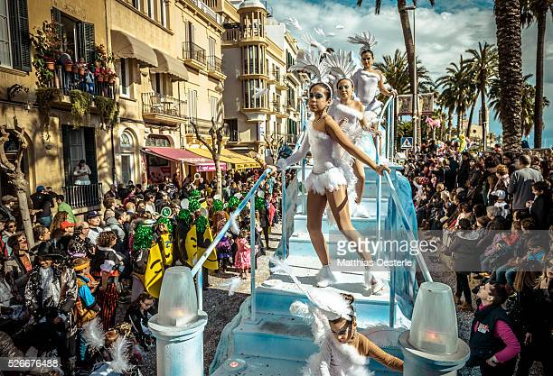 Revelers in their colorful costumes dance on their float during the children carnival parade in Sitges