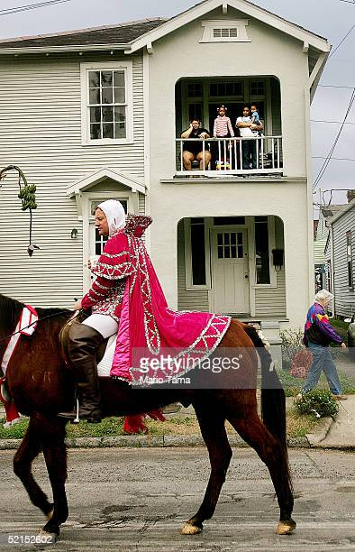 Revelers look on as a mounted horseman passes during the historic Proteus parade founded in 1882 during Mardi Gras festivites February 7 2005 in New...