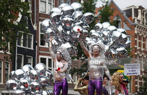 Revelers on a boat covered in glitters parade the Prinsengracht canal participating in the Amsterdam Canal Parade during Amsterdam Gay Pride on...