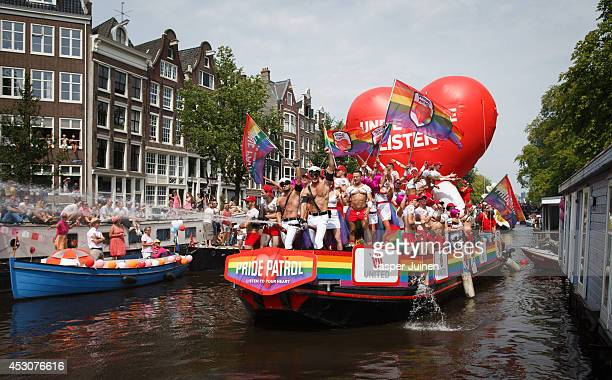 Revelers on a boat parade the Prinsengracht canal participating in the Amsterdam Canal Parade during Amsterdam Gay Pride on August 2 2014 in...