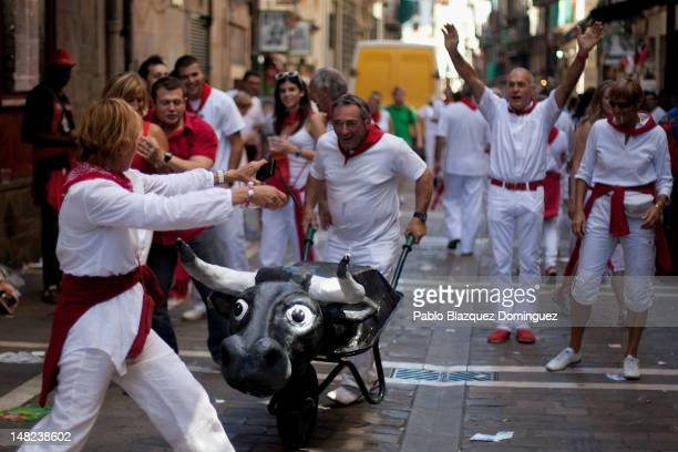 Revelers play with a trolley depicting a bull after the San Fermin runningofthebulls on July 12 2012 in Pamplona Spain Pamplona's famous Fiesta de...