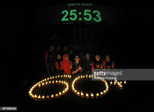 Revelers pose near burning candles displaying 60 during Earth Hour celebration at Sheraton Hotel on March 28 2015 in Surabaya Indonesia Millions of...