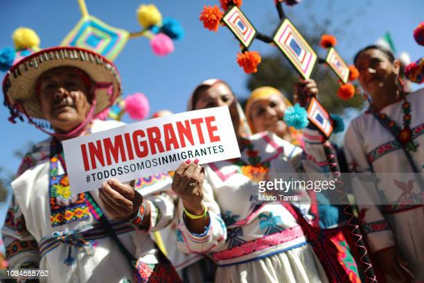 Revelers pose with a sign reading 'We Are All Immigrants' in Spanish during the 72nd annual East LA Mexican Independence Day Parade on September 16...