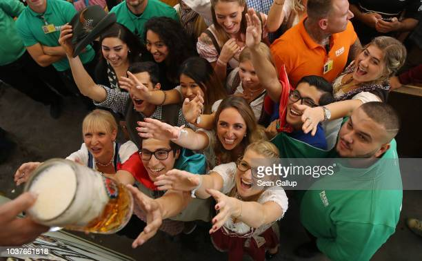 Revelers reach for a one liter mug of beer in the Paulaner tent shortly after the official opening of the 2018 Oktoberfest beer festival on September...