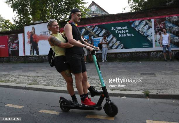 Revelers ride an electric scooter or escooter during the fifth edition of the annual 'Zug der Liebe' or 'Caravan of Love' event on August 24 2019 in...