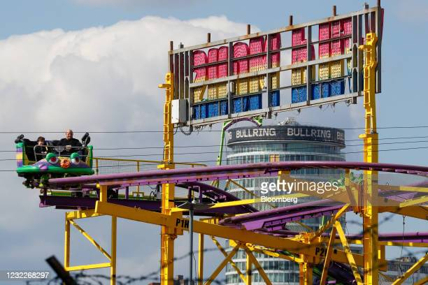 Revelers ride on a roller coaster at a fairground in Digbeth, in view of the Bullring Centre in Birmingham, U.K., on Monday, April 12, 2021....