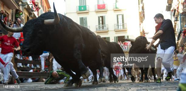 Revelers run with bulls from the Victoriano del Rio ranch along Estafeta street on the sixth day of the San Fermin runningofthebulls on July 12 2012...