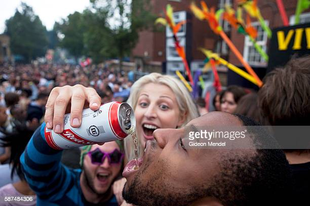 Revelers share some of the Jamaican Red Stripe beer while dancing at the Sancho Panza sound system which plays funky house music at the Notting Hill...