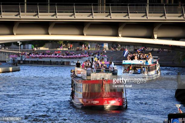Revelers stand on passenger ships in government district while they attend the annual Christopher Street Day boat parade on July 25 2019 in Berlin...