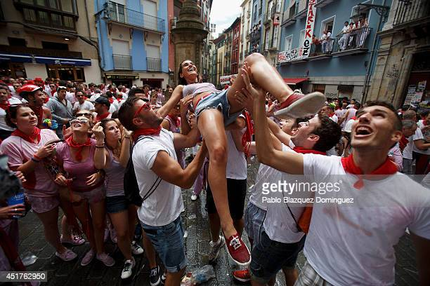 Revelers throw a woman to the air during the opening and the firing of the 'Chupinazo' rocket which starts the 2014 Festival of the San Fermin...