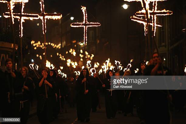 Revelers walk with burning crosses during the Bonfire Night celebrations on November 5 2012 in Lewes Sussex in England Bonfire Night is related to...