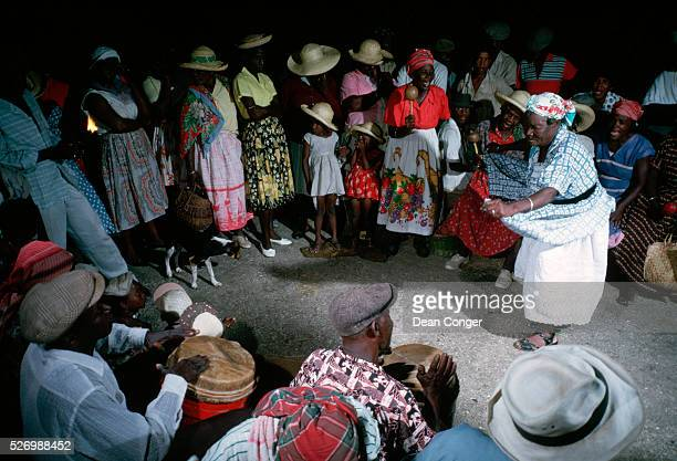 Revelers watch a woman dance to drum music at the Big Drum festival on Carriacou Island Grenadines
