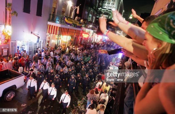 Revelers watch as police officers clear Bourbon Street at midnight at the official conclusion of Mardi Gras festivities February 9 2005 in New...