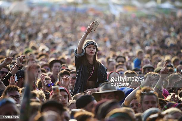 Revelers watch English band Jamie T perform on the Other Stage at the Glastonbury Festival of Music and Performing Arts on Worthy Farm near the...