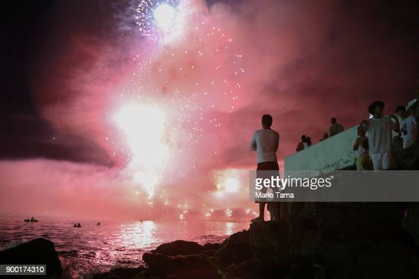 Revelers watch fireworks launched from barges explode over Copacabana beach on January 1 2018 in Rio de Janeiro Brazil Fireworks were launched in...