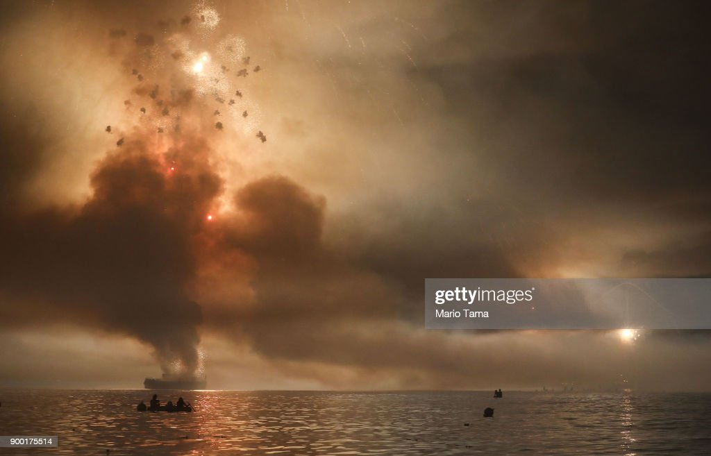 Revelers watch from a boat as fireworks are launched from barges over Copacabana beach on January 1, 2018 in Rio de Janeiro, Brazil. Fireworks were launched in cities worldwide to ring in 2018.